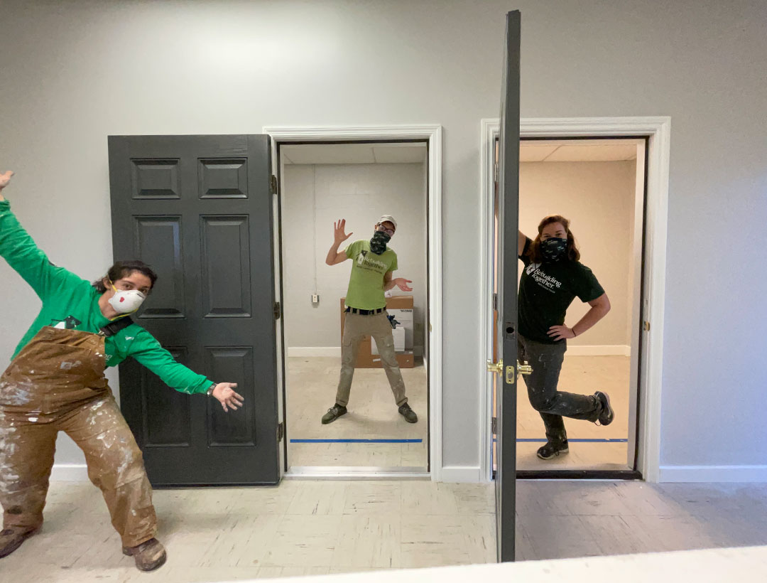 R.D., masked, standing and posing in a door frame between the two current AmeriCorps members on either side of him. One member is posing with arms outstretched to sides and the other is leaning against another door frame. They are all inside an empty office space.