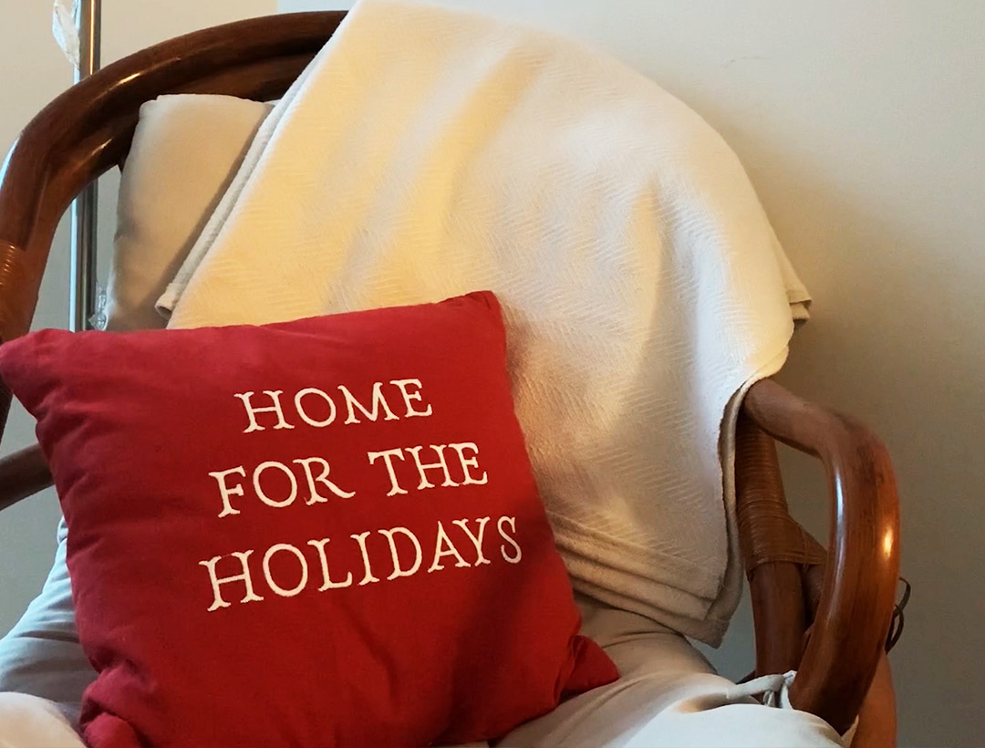 "A pillow with ""Home for the Holidays"" written on it sitting on a chair"