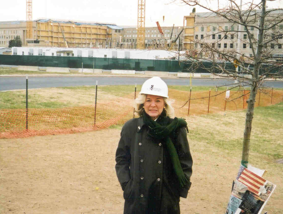 Patty Johnson standing in a white Rebuilding Together hard hat in front of the Pentagon.