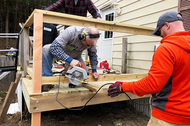 Volunteer uses circular saw while building ramp