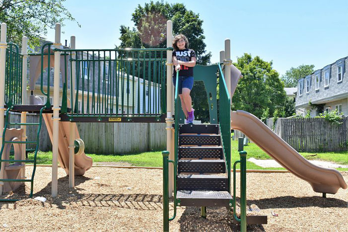 """Middle schooler, Keira Ugaz, takes time out from """"exercising"""" to pose on the newly installed community playground located on Still Meadows Drive in Severn on July 15, 2019."""