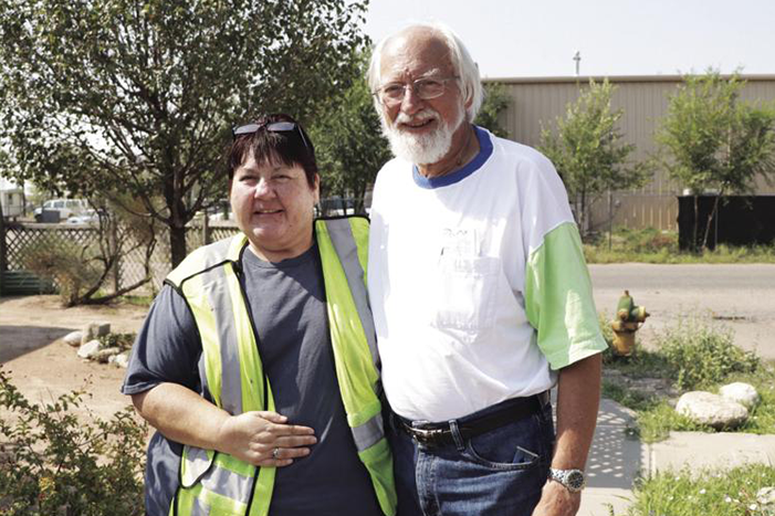 Homeowner Ancilla Quintana, left, stands next to Jerry Saxton, volunteer and board member for Rebuilding Together at Southern Sandoval County. Saxton helped install the new swamp cooler on Quintana's roof.