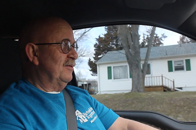 Frank in a Rebuilding Together tshirt driving through Muscatine County